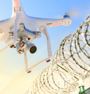 Drone with camera just outside a barbed wire fence