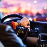 Man in car with hand on the wheel